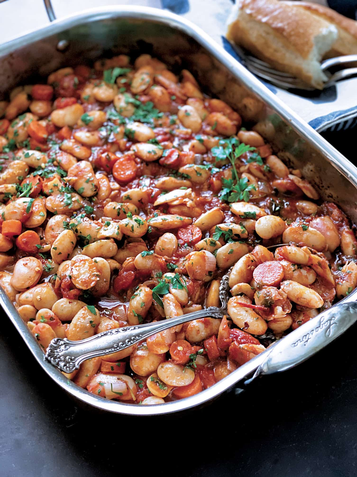 A large baking pan with cooked gigantes beans, carrots, fresh parsley. A napkin with serving utensils and pieces of bread on the side.