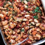 A large baking pan with cooked gigantes beans, carrots, fresh parsley.