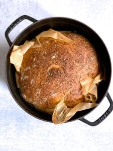 A black dutch oven with parchment paper and baked bread loaf in it on a cement surface.