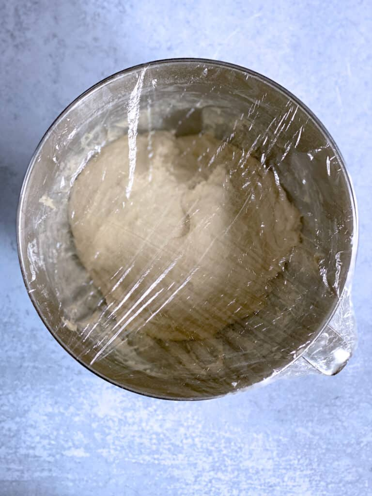 A metallic bowl with flour covered with plastic film on a cement surface.