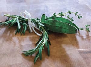 Fresh herbs tied together on a cutting board.
