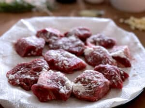 Pieces of beef for stew on a paper towel with flour sprinkled on them.