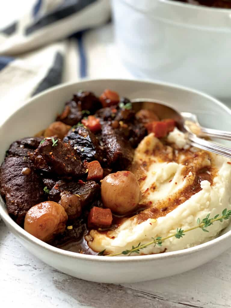 A plate with beef stew and mashed potatoes. At the back a white pot and a cloth napkin.
