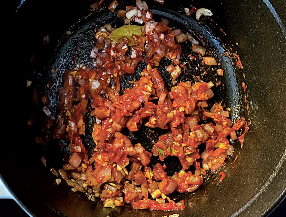 Diced onons and carrots with tomato paste in a pot.