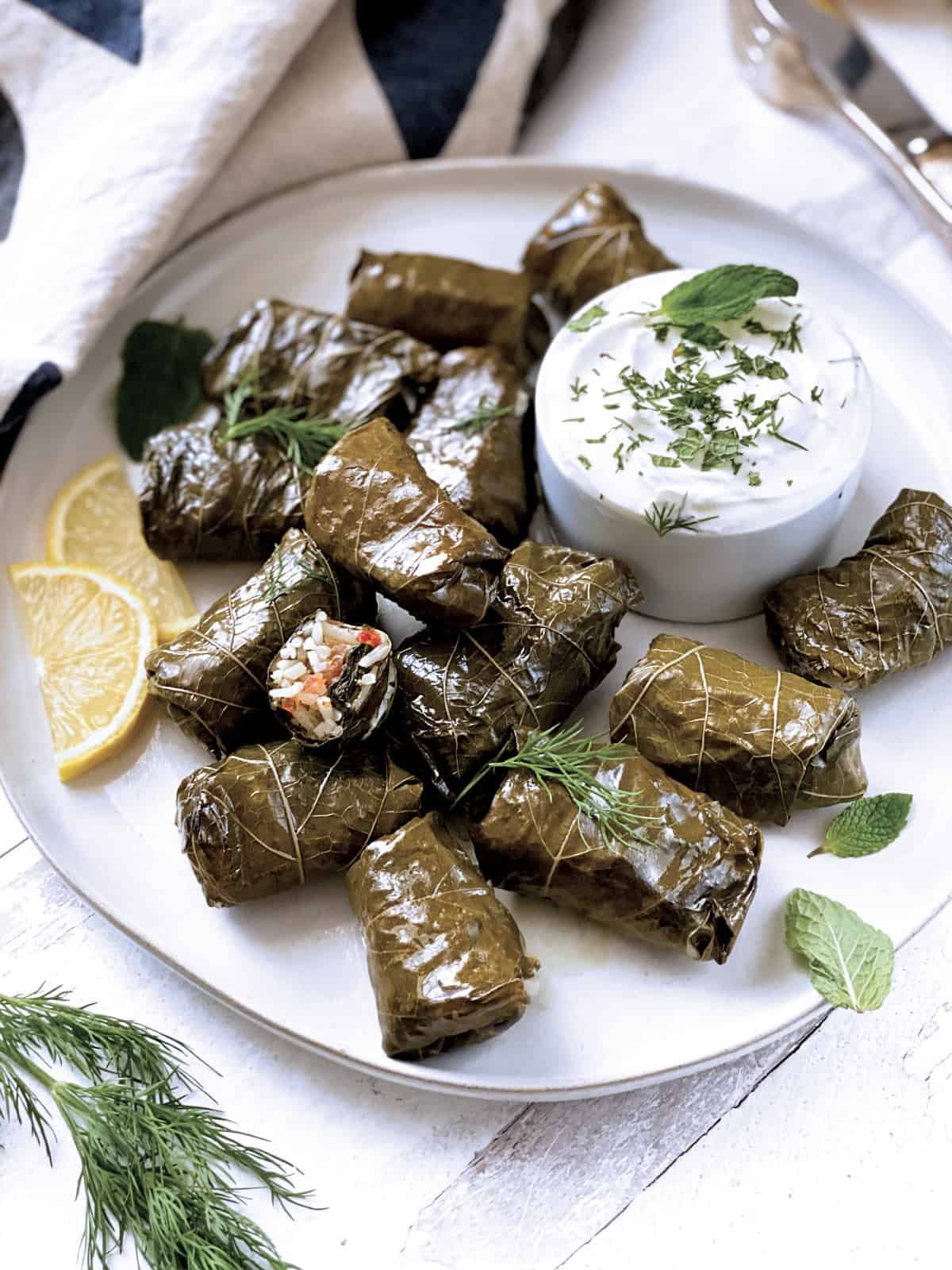 A plate with stuffed grape leaves, and a bowl of yogurt sauce. Fresh dill leaves at the from, a cloth napkin and utensils at the back.