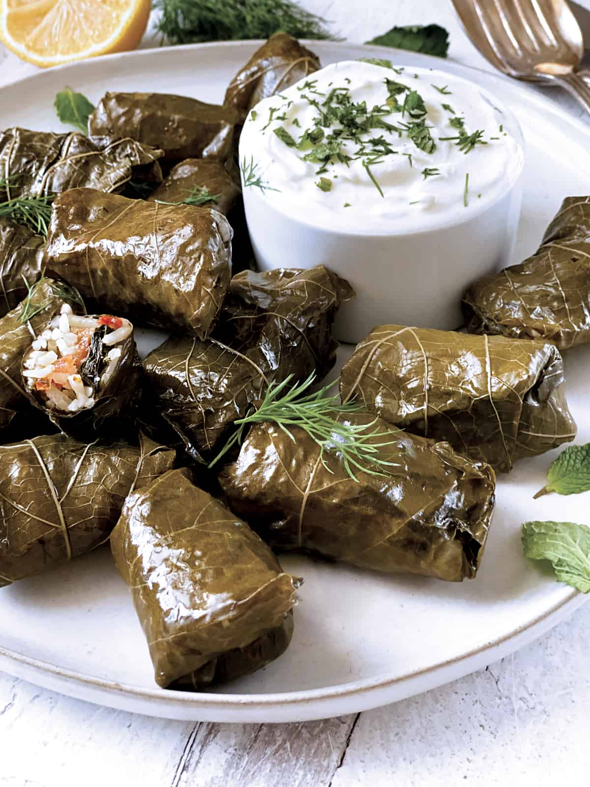 A plate with dolmades, and a bowl of yogurt sauce. Fresh dill leaves at the from, a cloth napkin and utensils at the back.