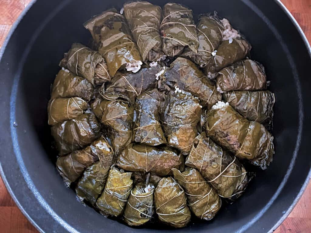 A black pot with cooked dolmades.