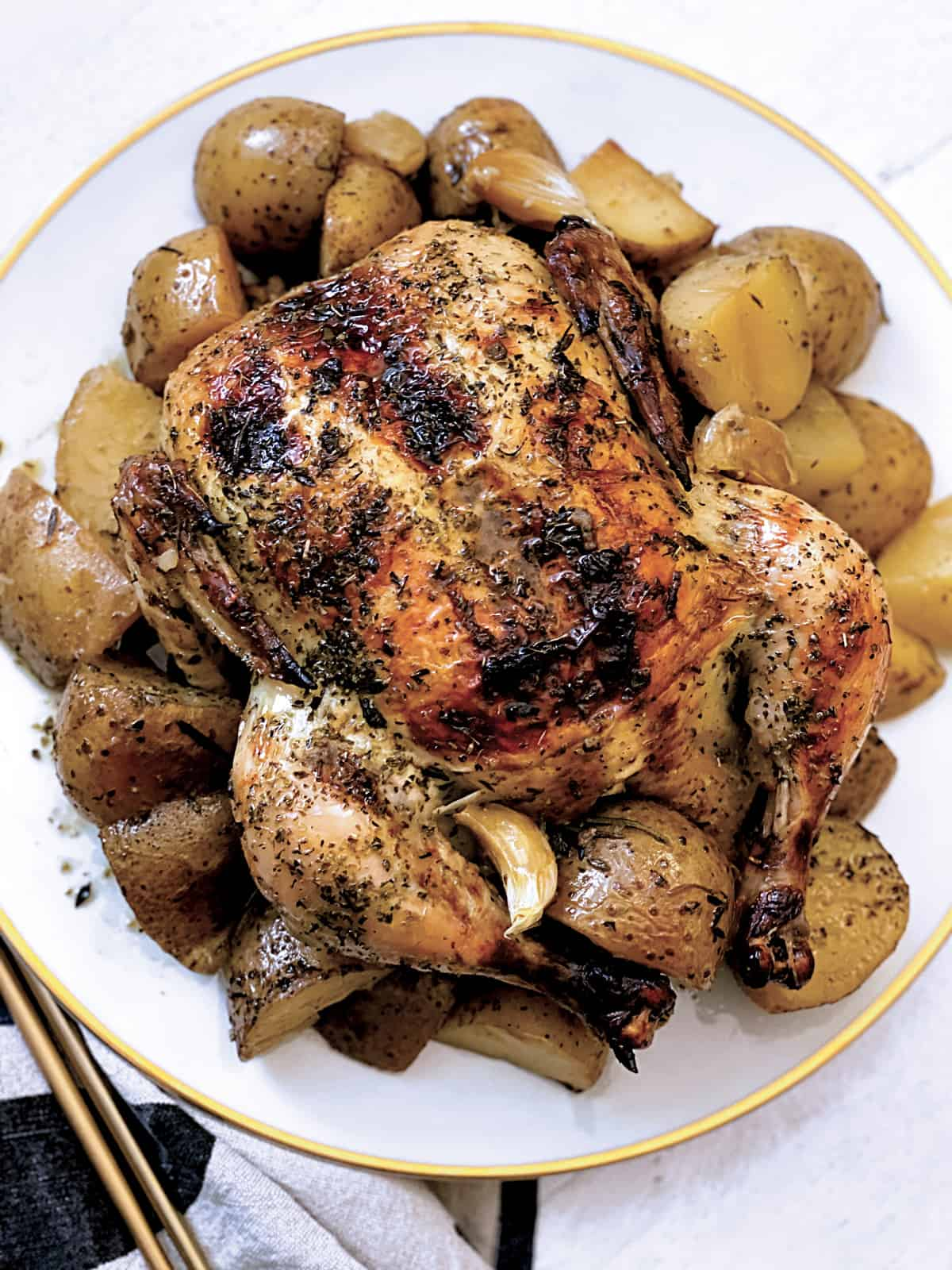 A roast whole chicken with potatoes on a platter with a cloth napkin and serving utensils.