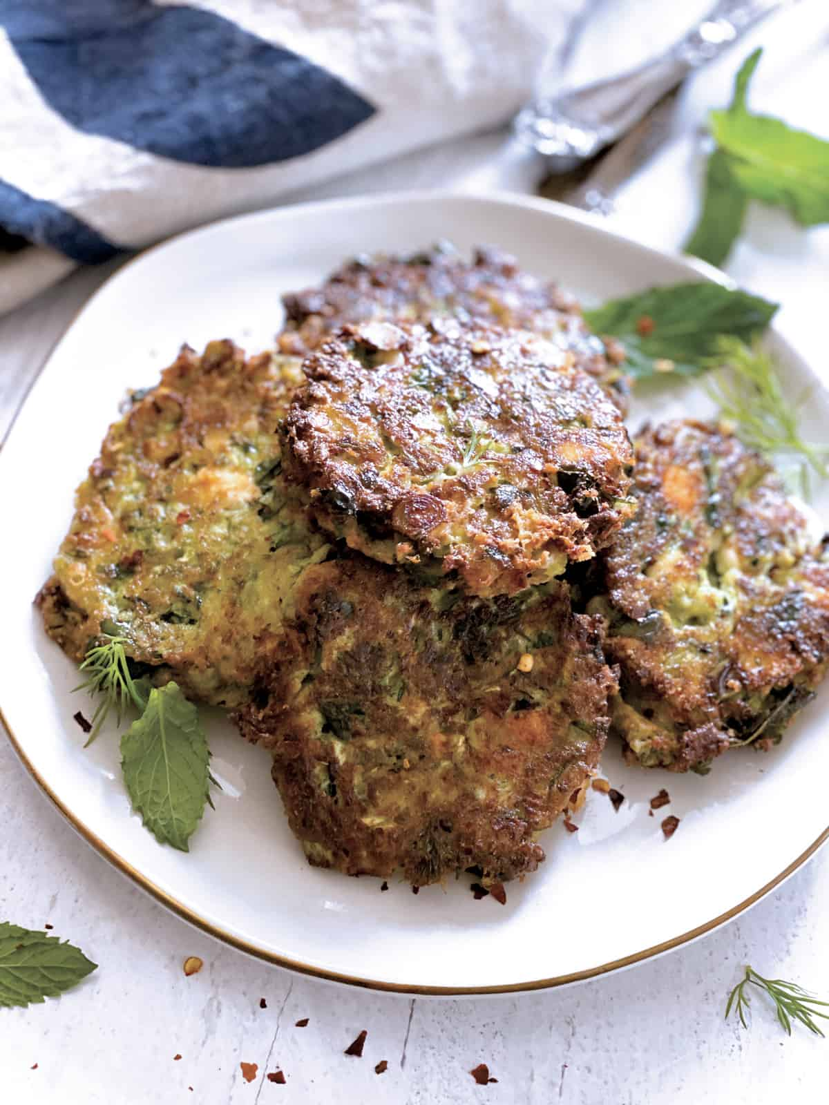 A plate with zucchini patties, utensils and a cloth napkin at the back.