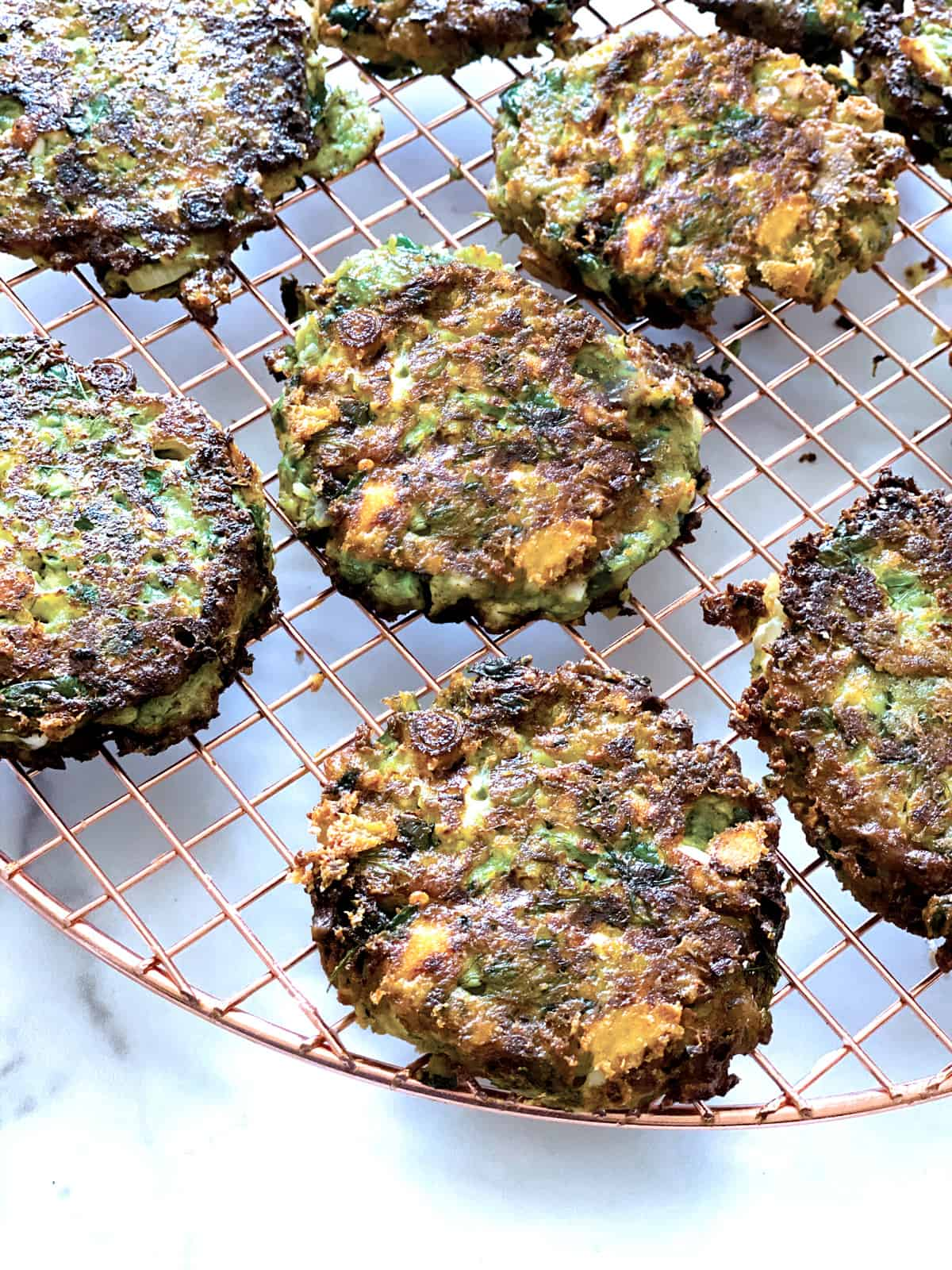 Zucchini pancakes on a wire rack.