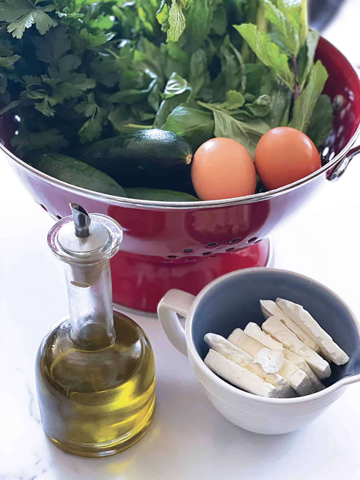 Fresh herbs, zucchini eggs and scallions in a red colander. In front, a glass bottle with olive oil and a cup with feta cheese.