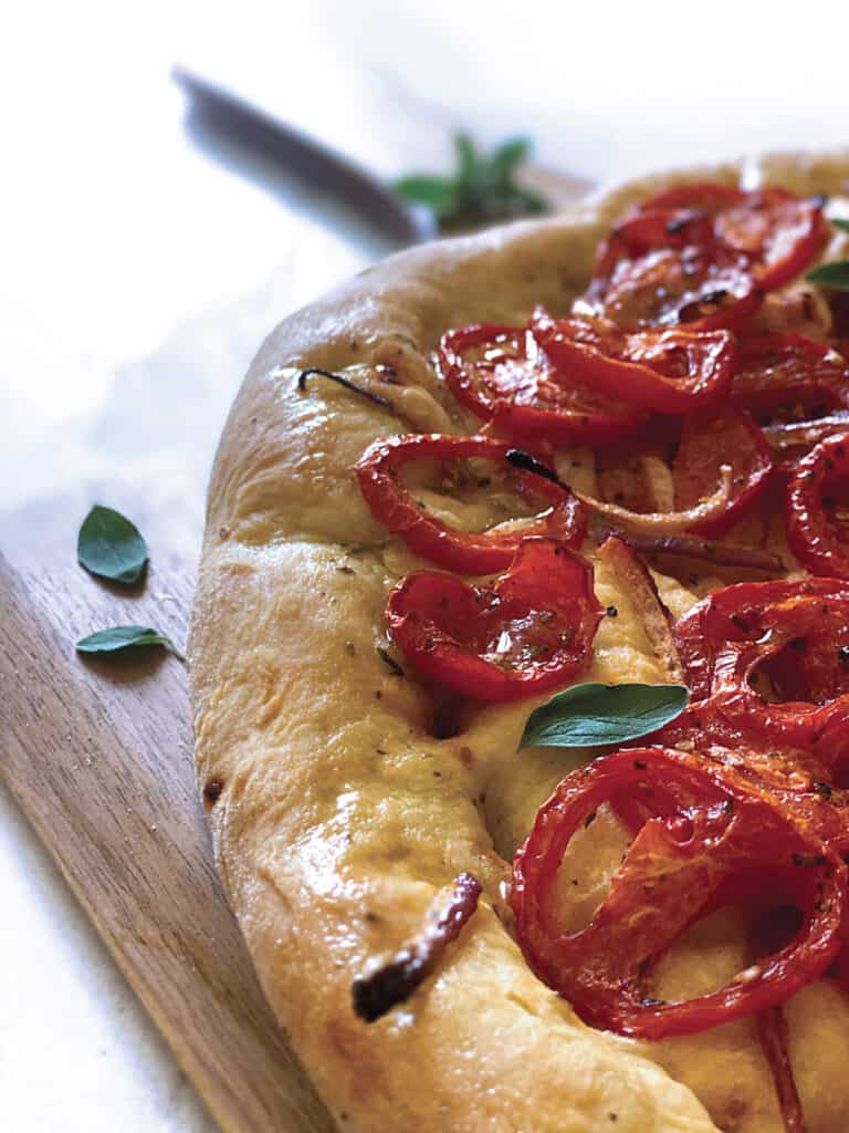 Side view of A Ladenia-vegan greek pizza on a pizza peel and a cloth napkin.