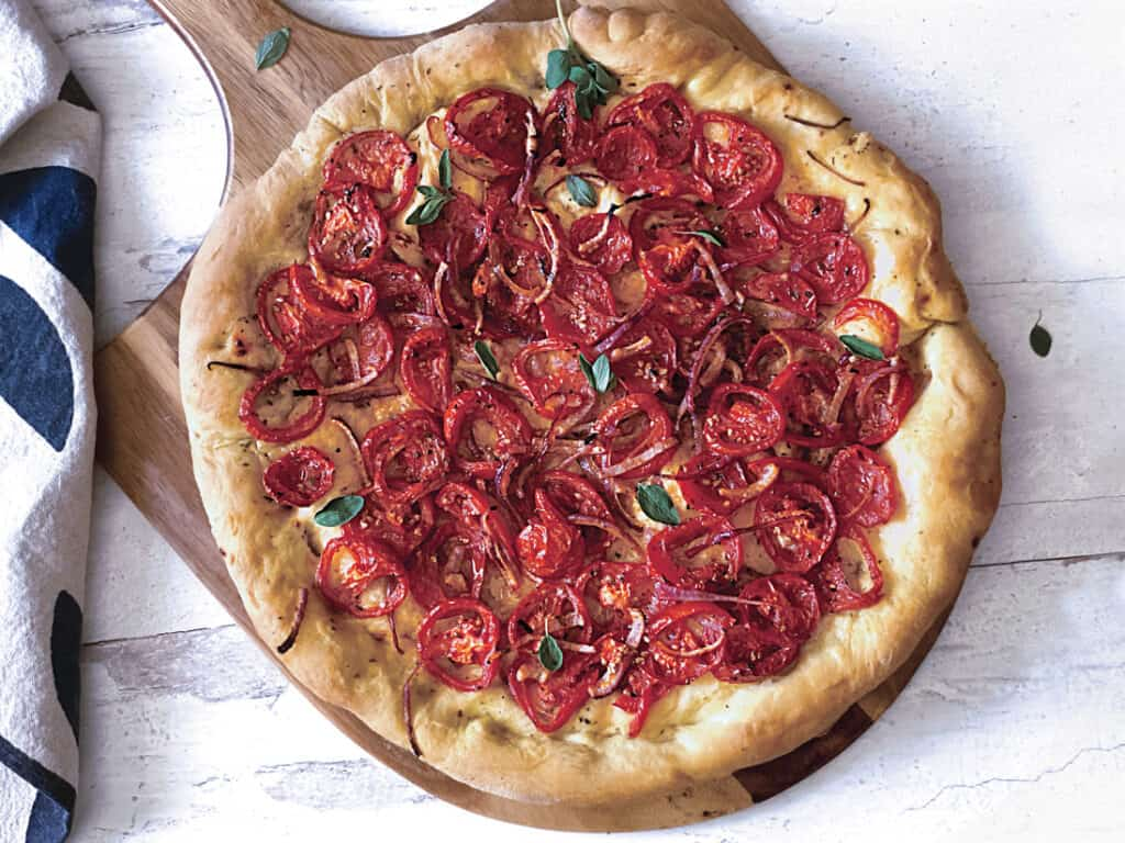 A Ladenia-vegan greek pizza on a pizza peel and a cloth napkin.