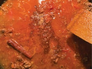 Tomatoes in a ground meat sauce and a wooden spoon.