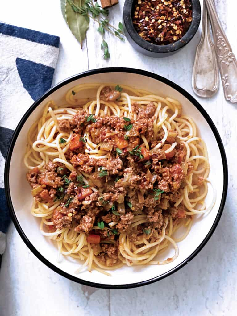 A plate with greek spaghetti with meat sauce, a bowl with red chili peppers, some fresh herbs, utensils and a cloth napkin.