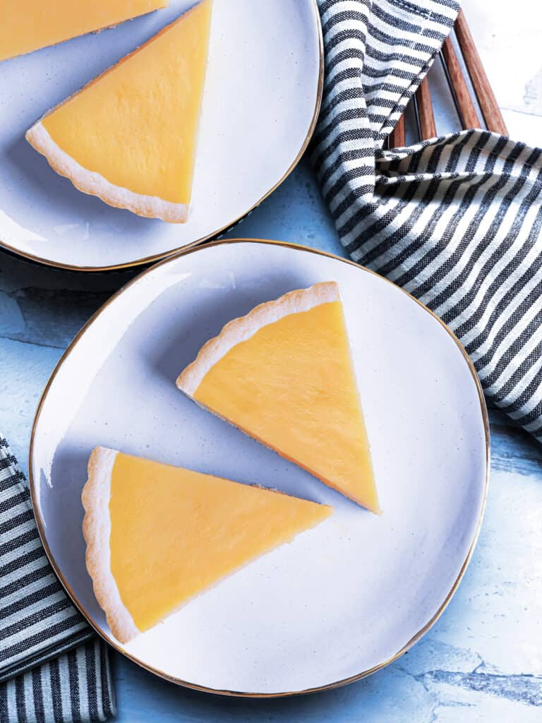 Two plates with pieces of lemon tart on them, utensils and two cloth napkins.