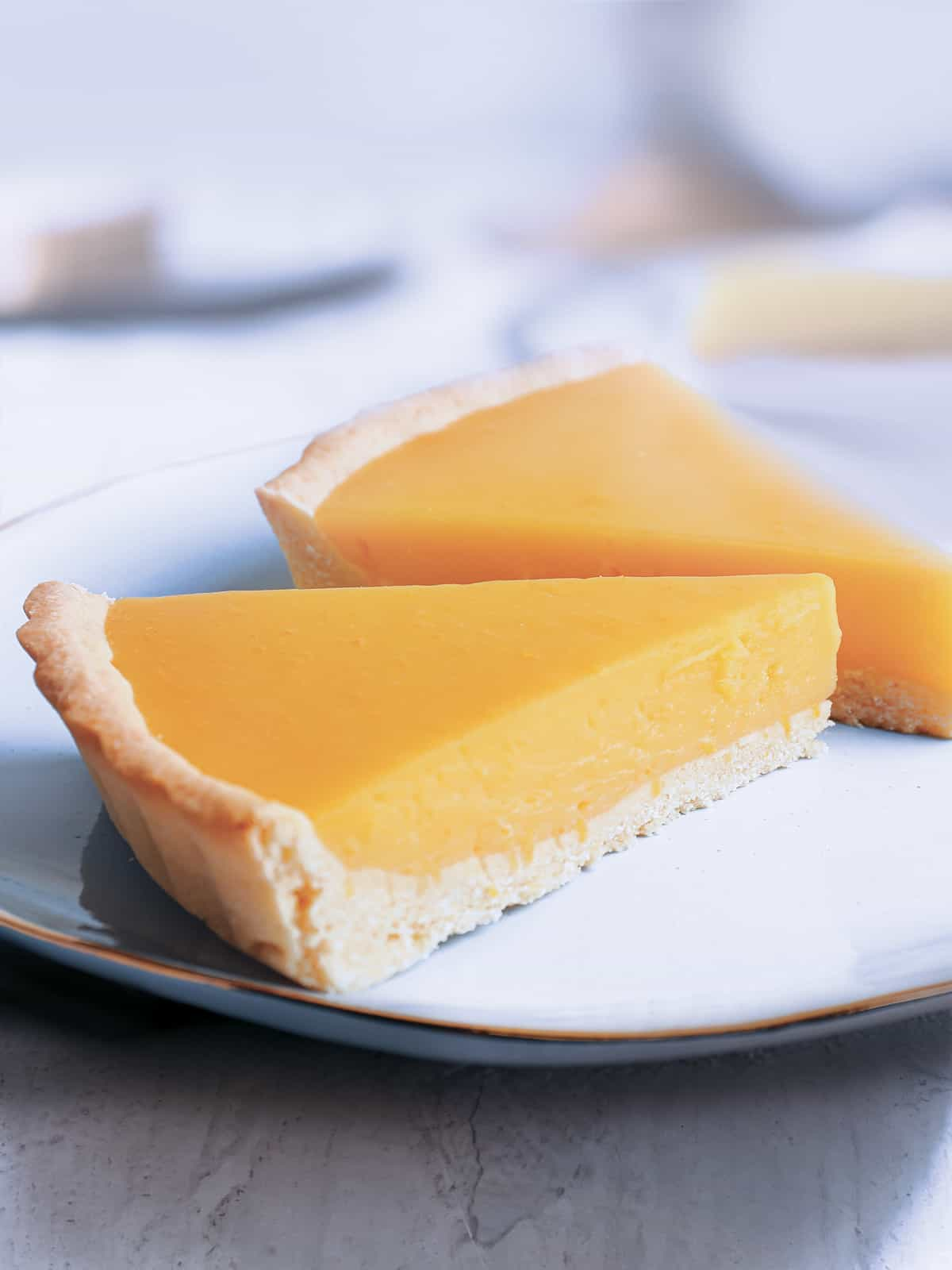 Two pieces of lemon tart on a plate.