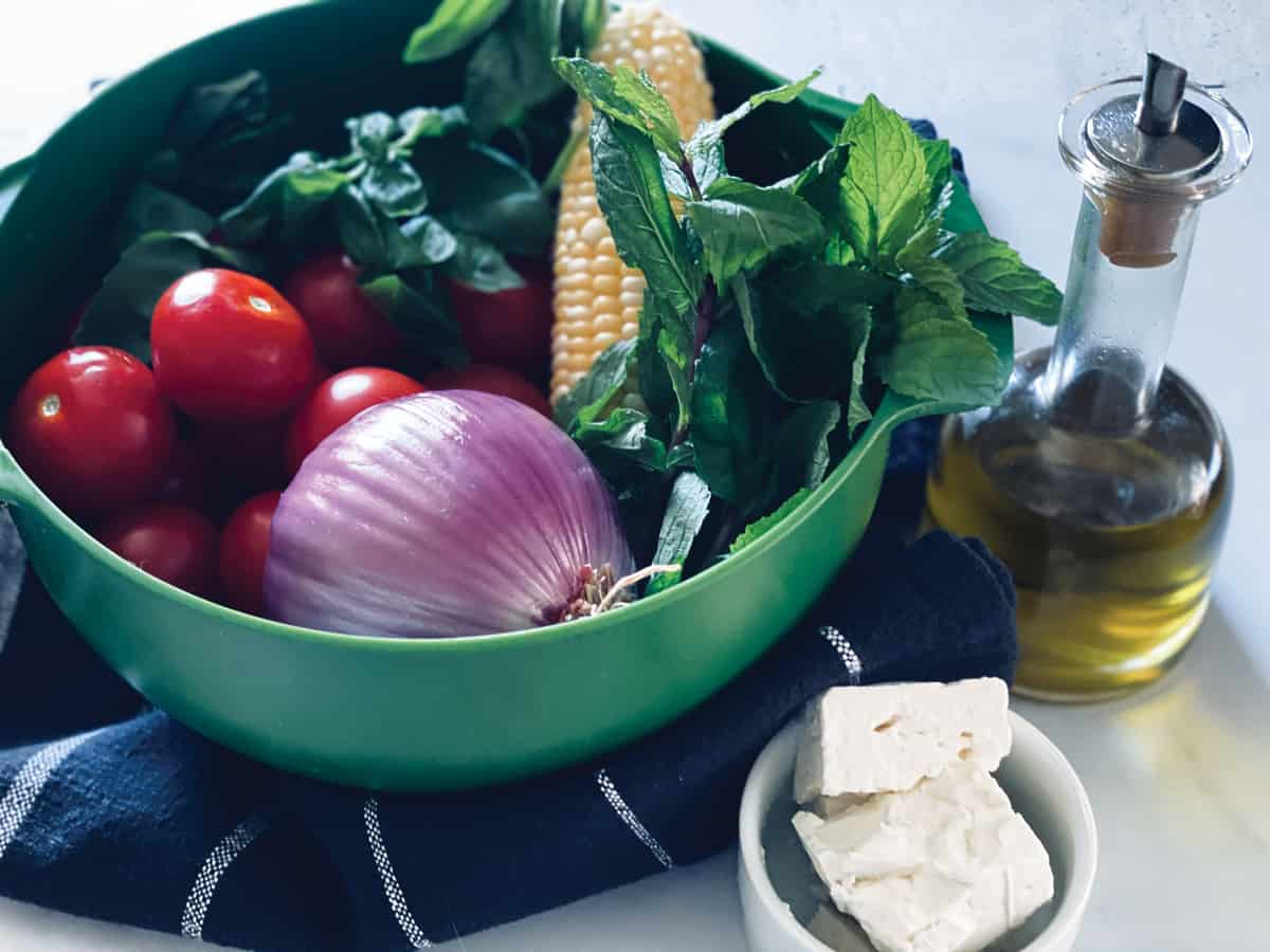 A green colander with tomatoes, an onion, corn and fresh herbs to make a  corn fritter recipe. Next to it a bottle with olive oil and a small bowl with feta cheese.