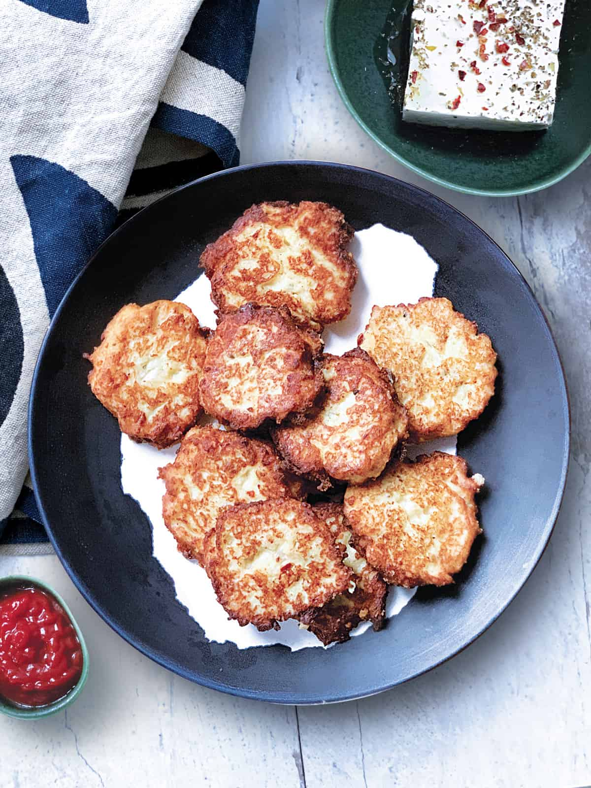 Aplate with cauliflower fritters, a bowl with feta cheese and a small container with ketchup. A cloth napkin at the back.