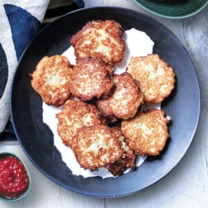 A plate with cauliflower fritters, a bowl with feta cheese and a small container with ketchup. A cloth napkin at the back.