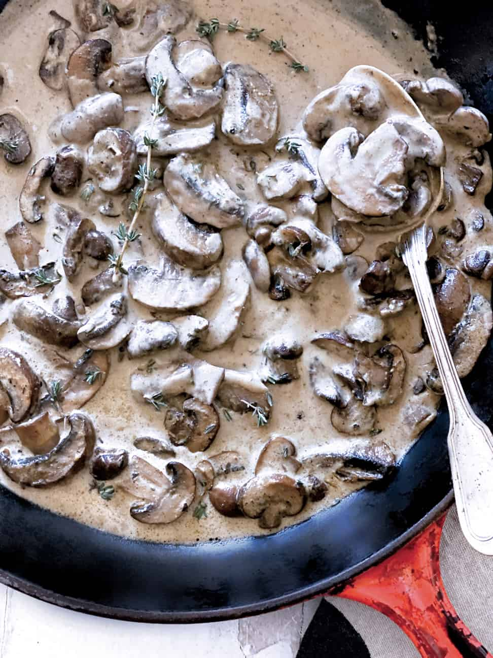 A red pan with mushroom sauce and a spoon on a napkin.