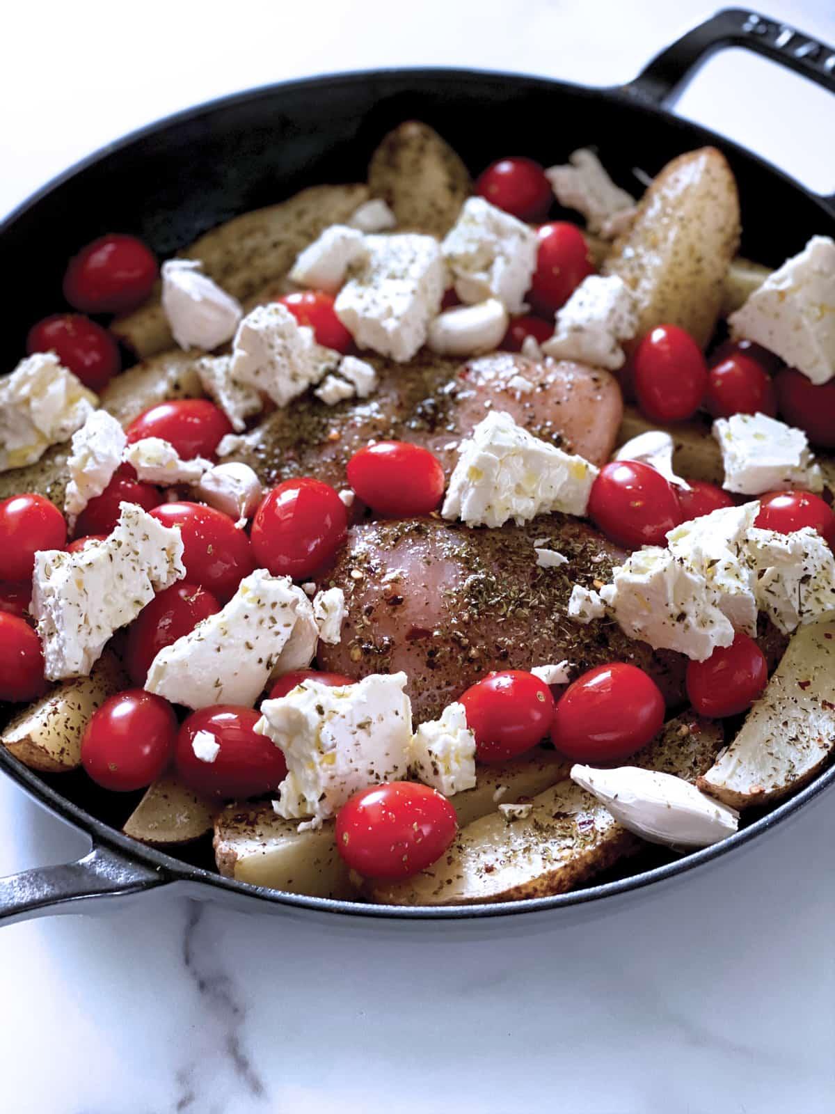 Chicken breast, cherry tomatoes, garlic cloves, potato wedges in a round black pan.
