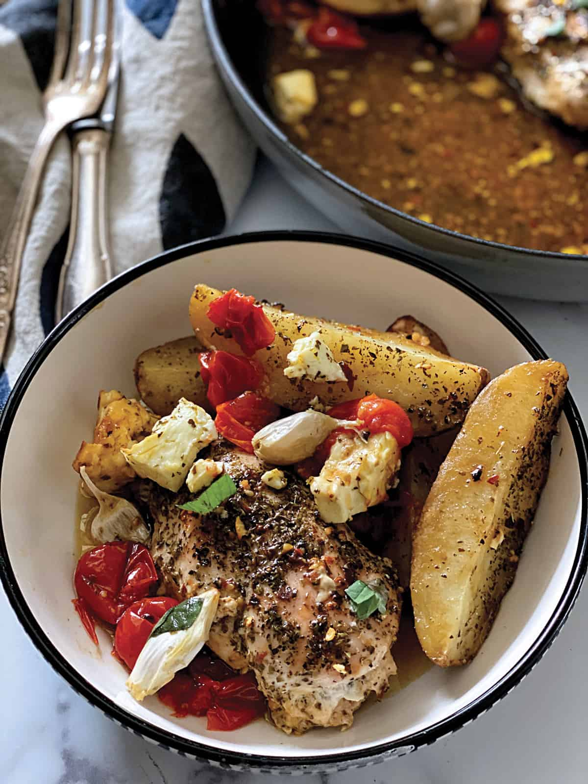 A plate with a baked chicken breast with herbs, potato wedges, roasted cherry tomatoes and pieces of feta cheese and garlic.