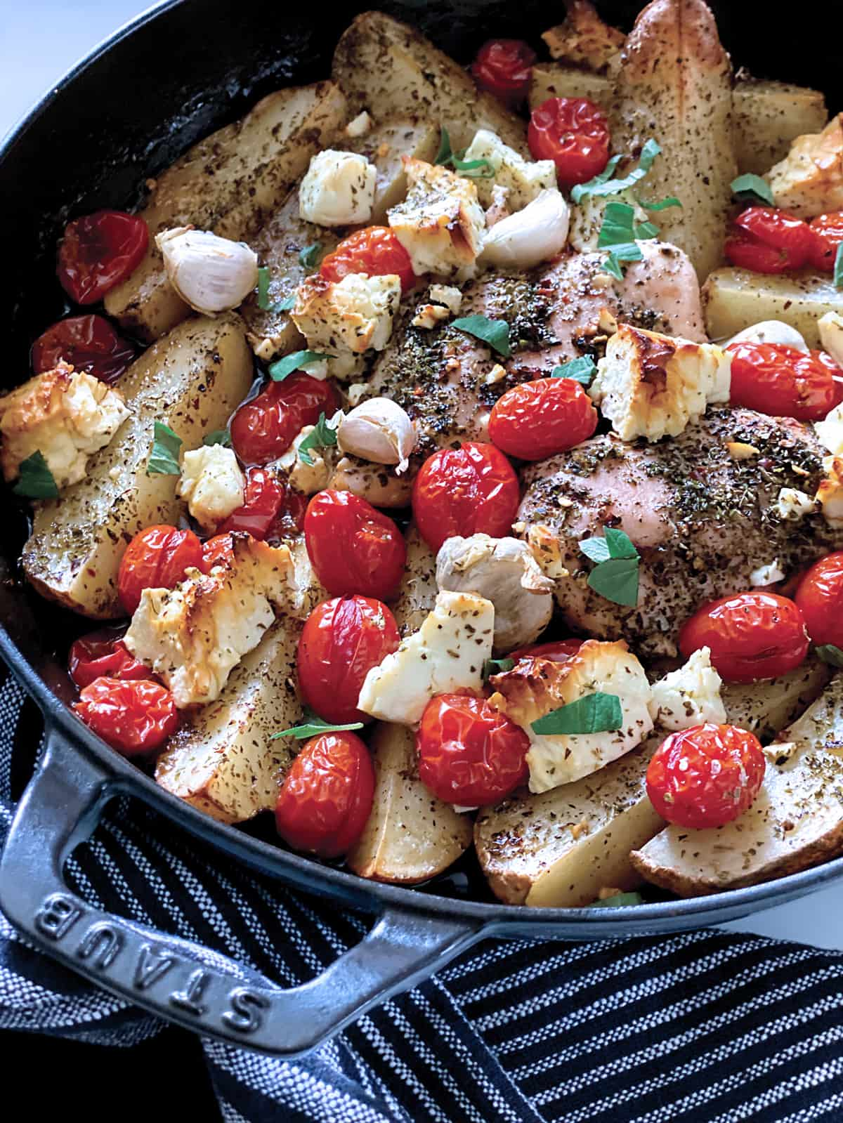 A round pan with Greek chicken and potatoes, roasted cherry tomatoes and pieces of feta cheese and garlic.
