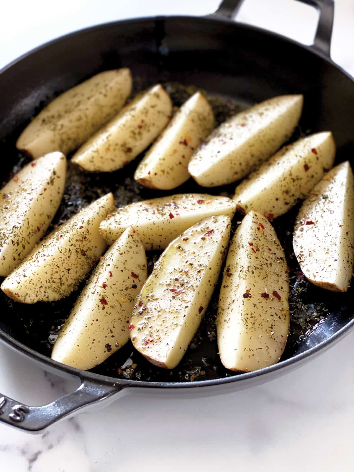 Raw potatoes cut in wedges in a black baking pan seasoned with oregano and pepper and olive oil.
