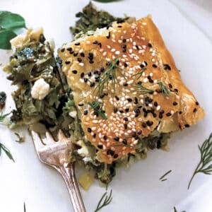 A piece of Greek Savory Pie in a white plate and a fork.