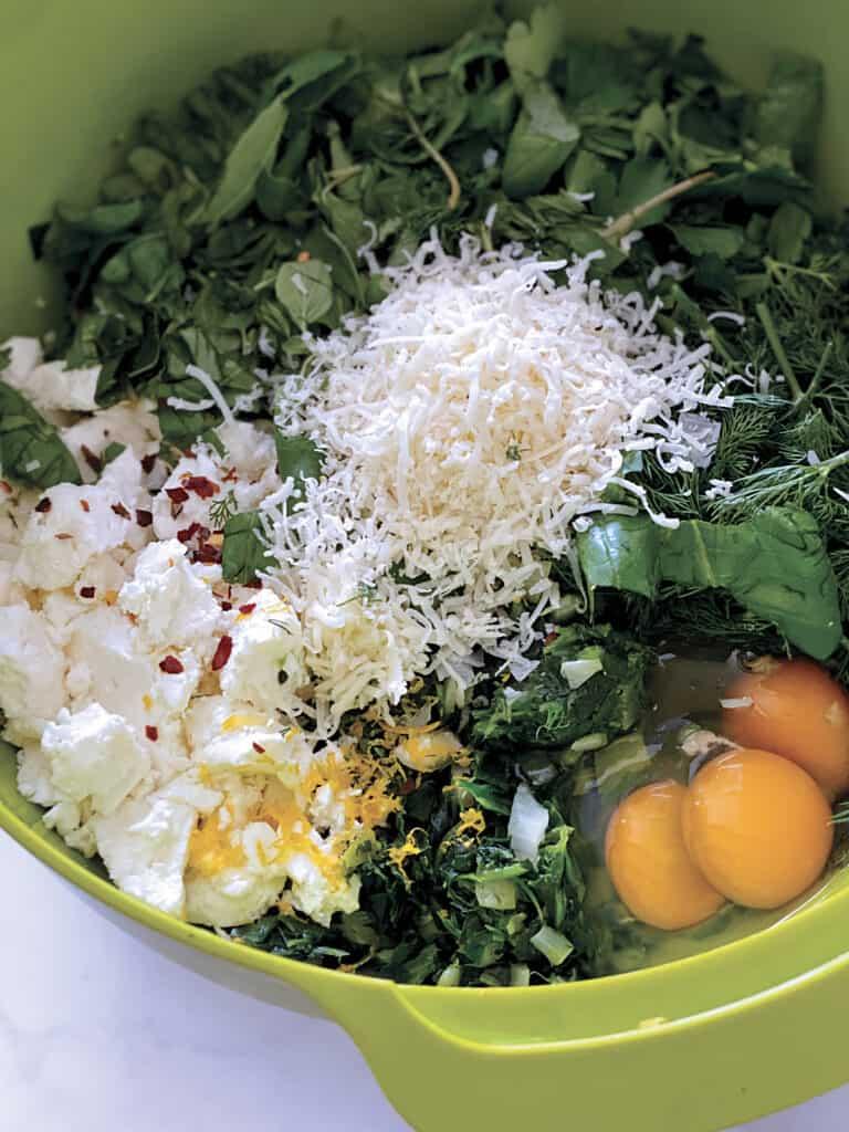 greens, eggs, feta lemon zest in a green bowl.