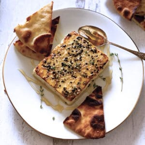 A block of roasted feta cheese with sesame seeds, honey and fresh thyme on a white plate with a spoon and cut up pita breads.