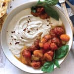A bowl with whipped feta and roasted tomatoes. Some pita bread , peppers and a cloth napkin.
