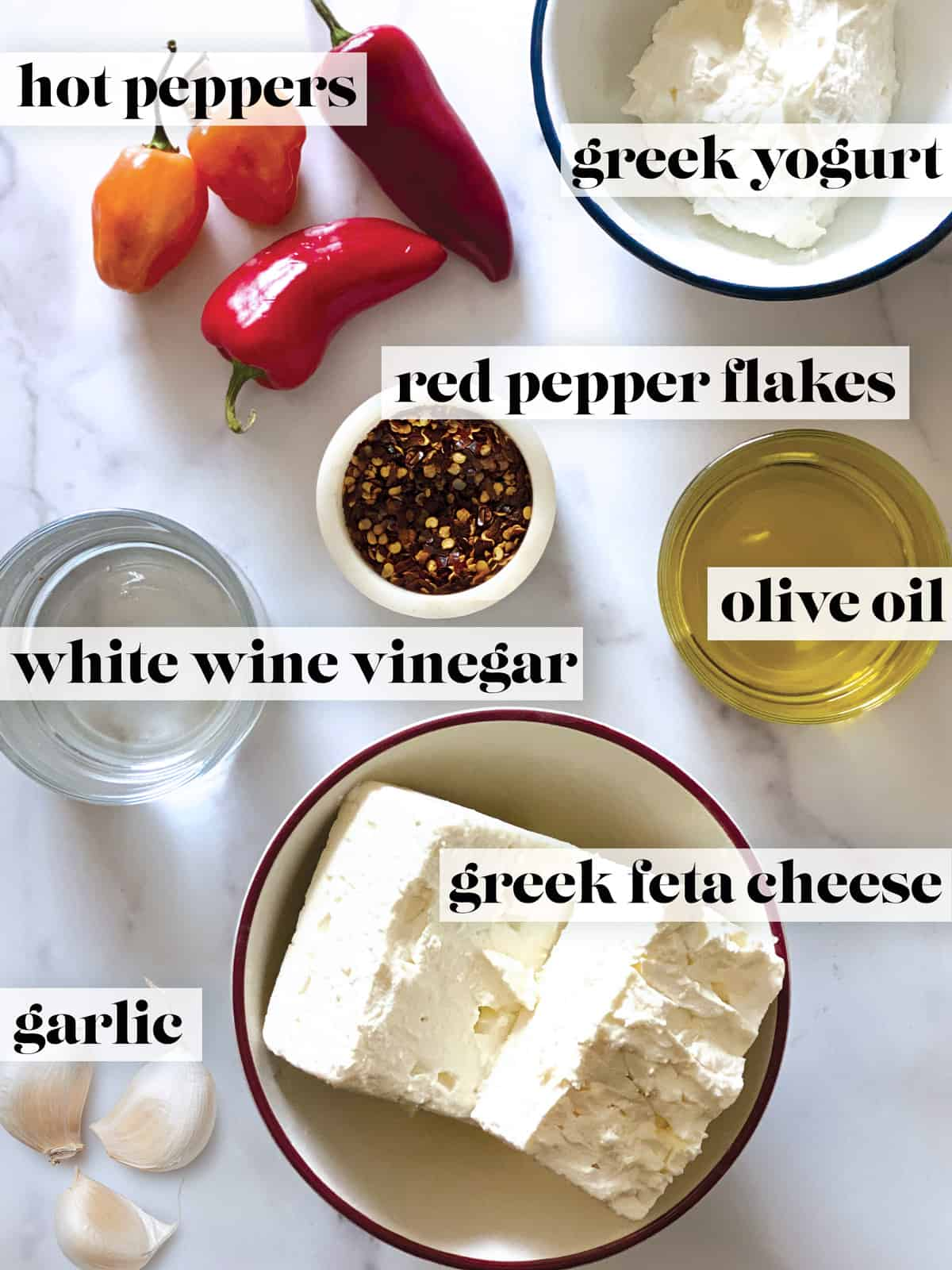 Hot red peppers, a bowl with yogurt, a container with pepper flakes, a glass with olive oil and a glass with vinegar, a bowl with feta, and a garlic cloves.