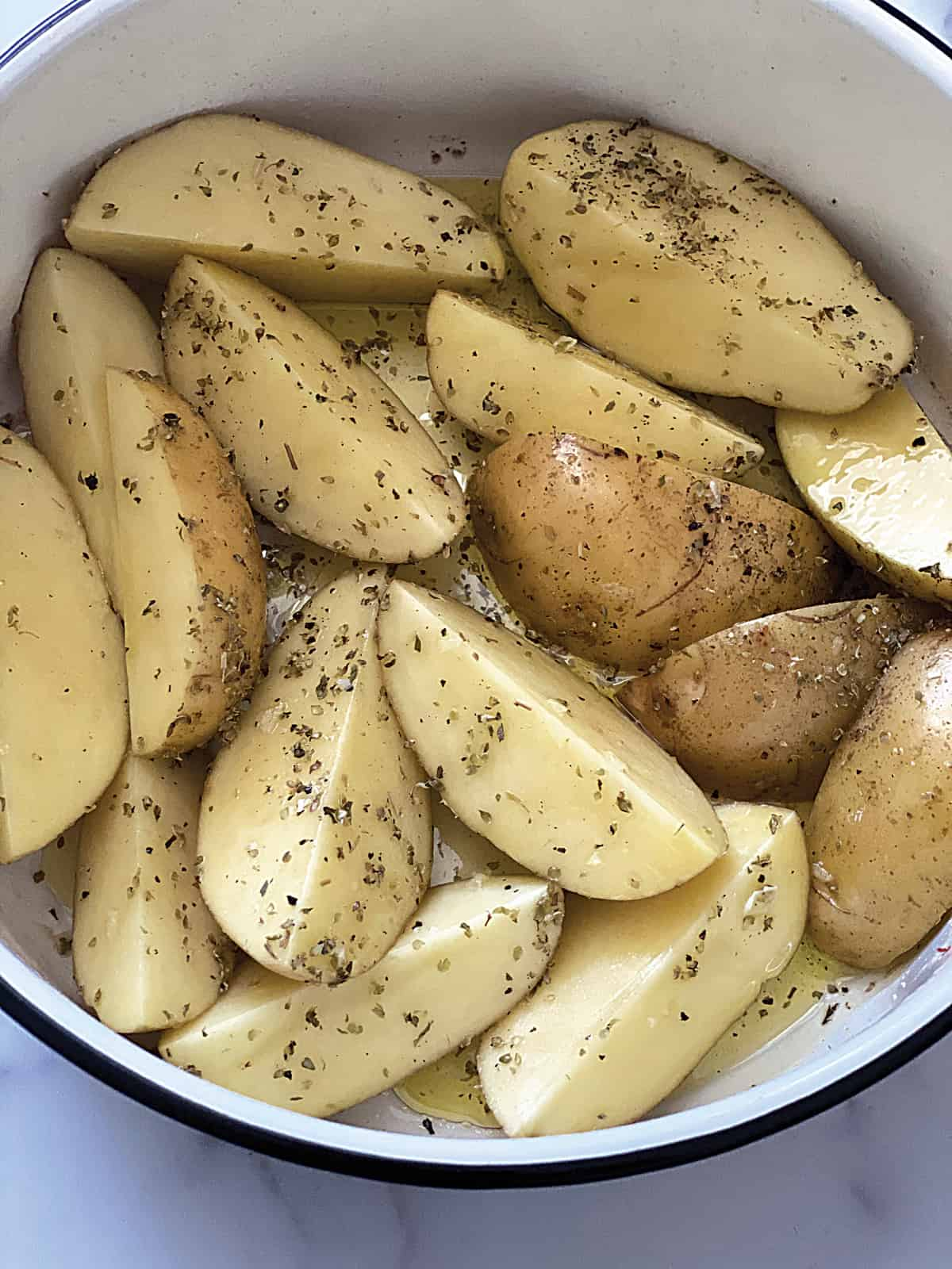 Potato wedges dressed in olive oil in a bowl.