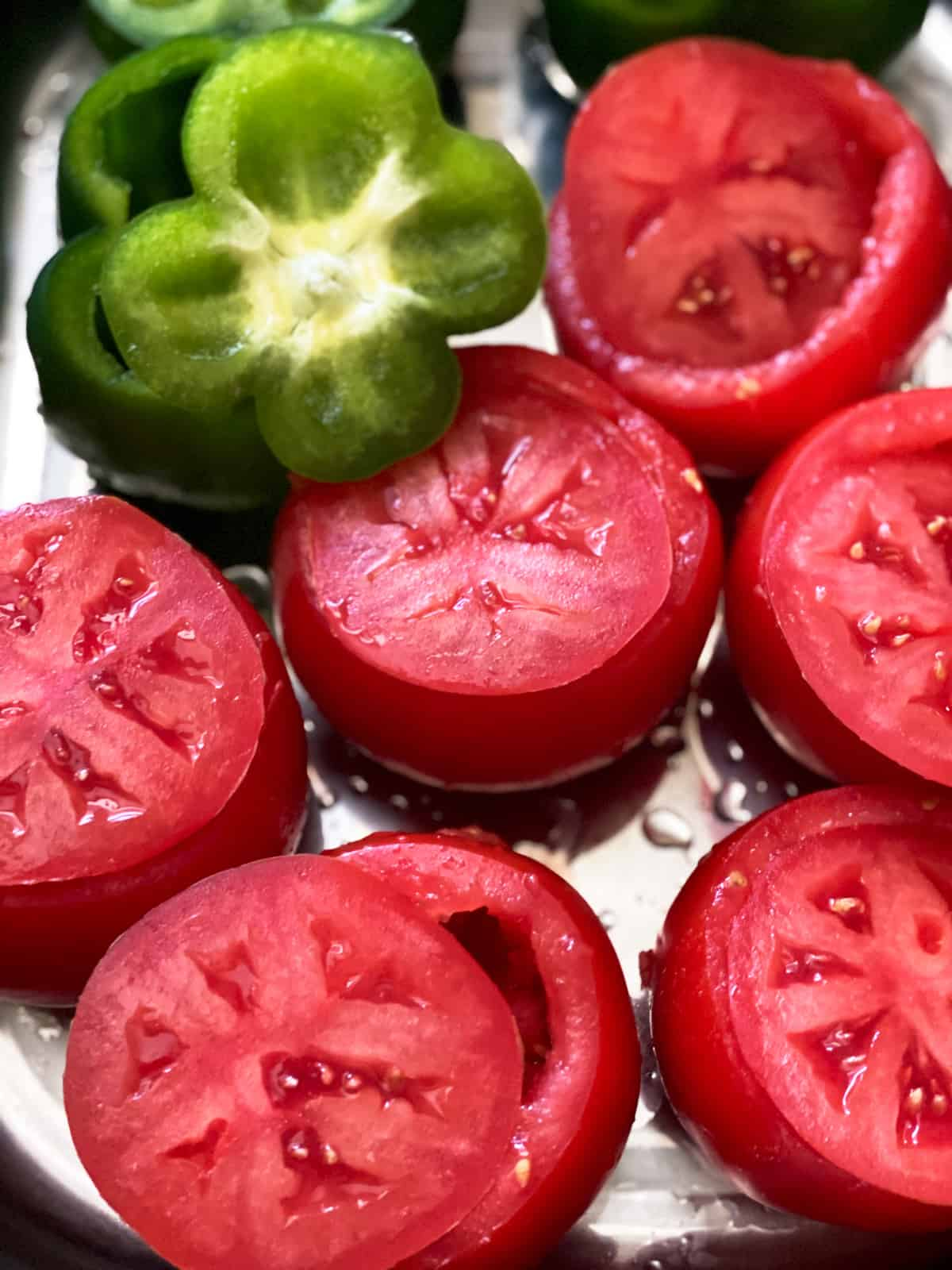 Tomatoes and green bell peppers with the tops cut, on top of each one.
