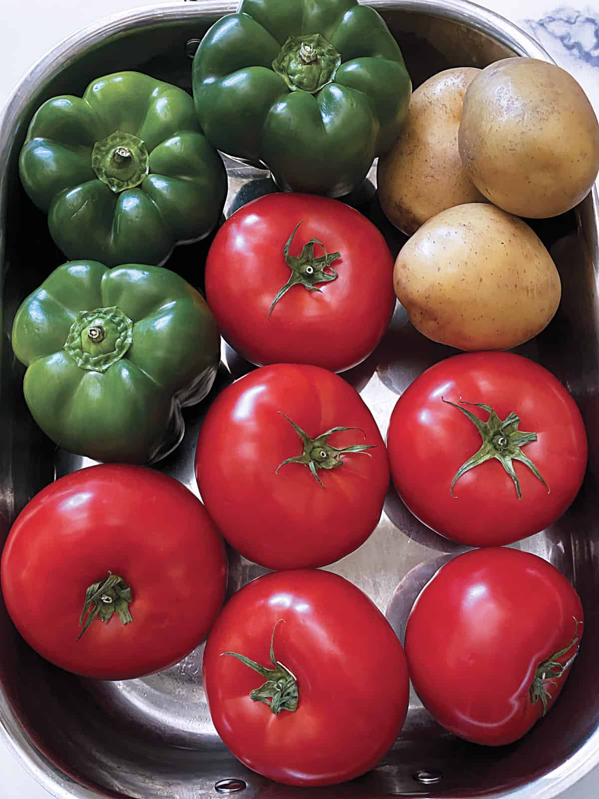 Tomatoes, green bell peppers and potatoes in a baking pan.