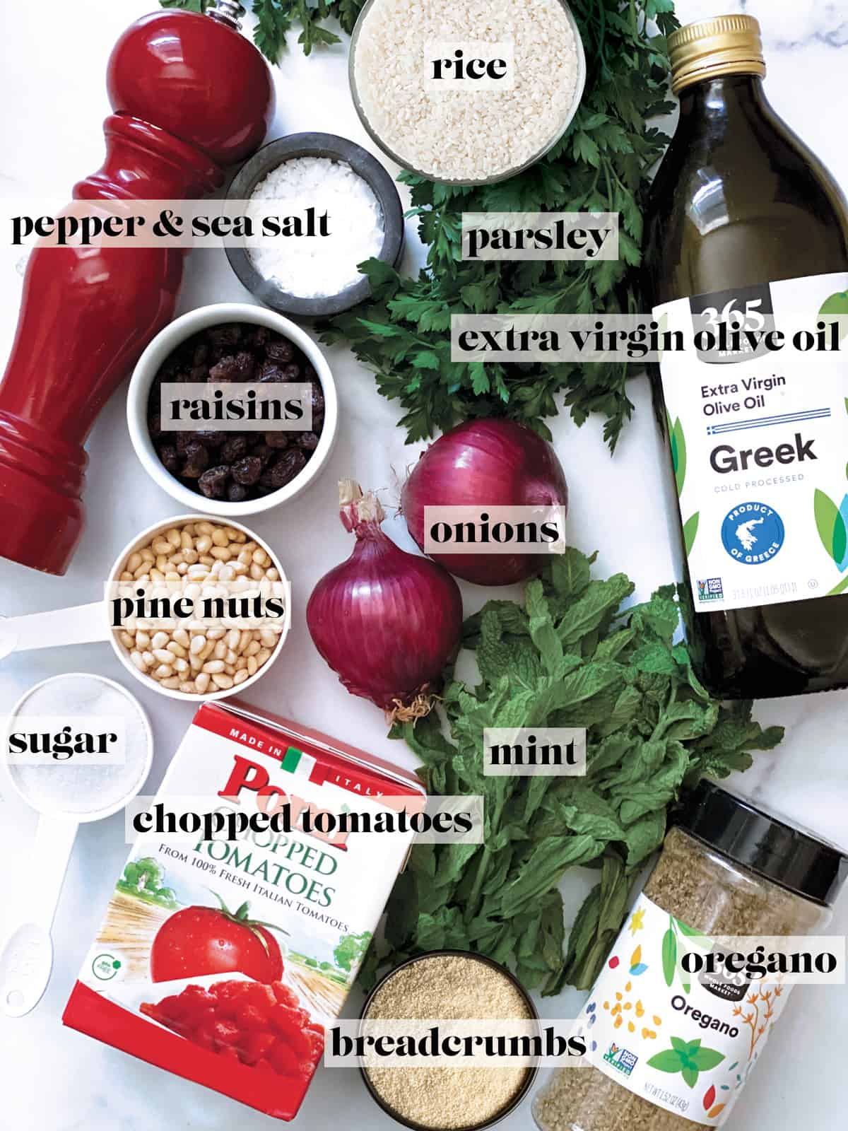 A pepper mill, small bowls with salt, pine nuts, sugar, rice, breadcrumbs, a box of chopped tomatoes, fresh herbs, a bottle of olive oil, two onions and a box with dry oregano.