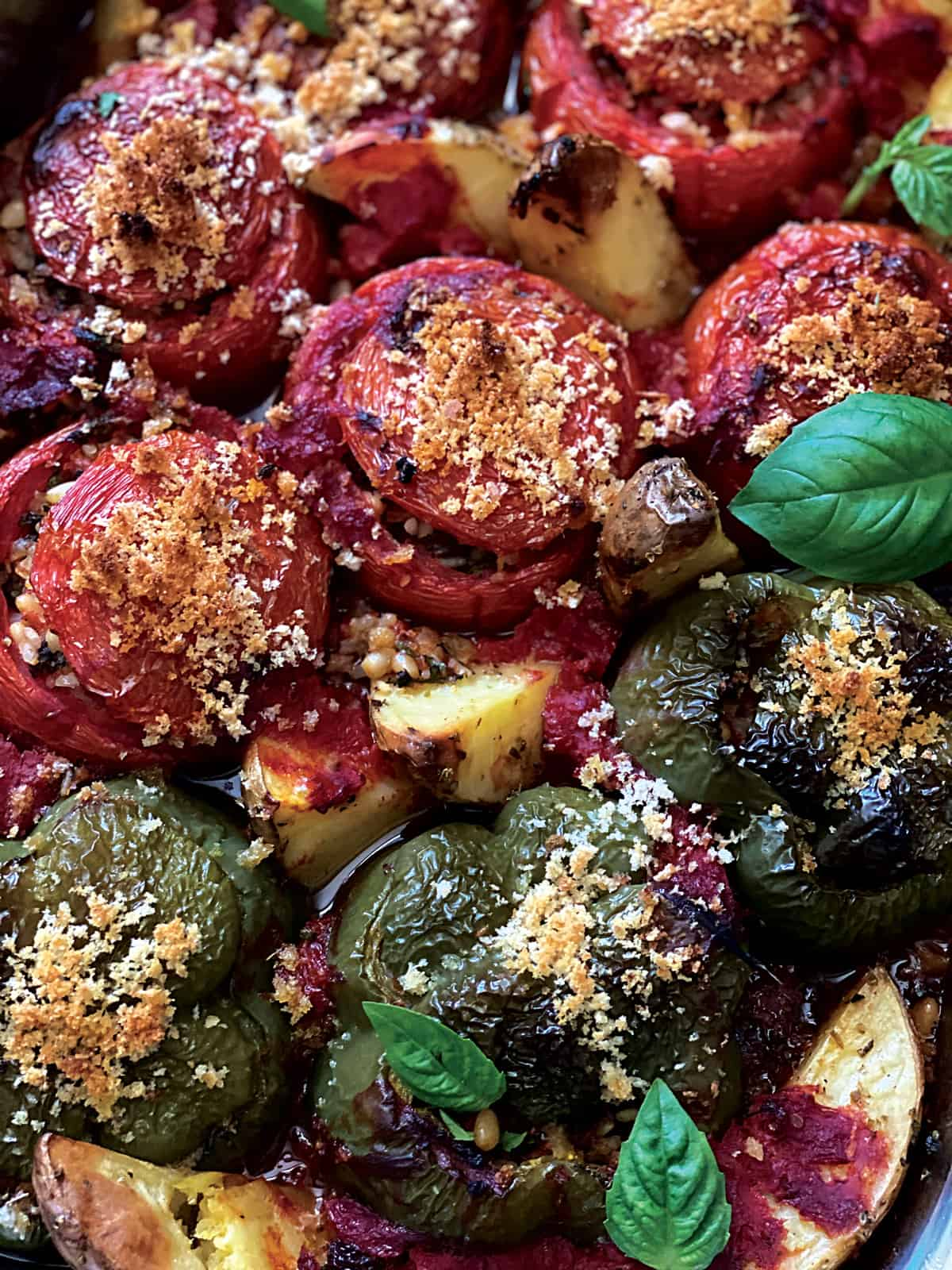 Stuffed tomatoes, bell peppers and potatoes in a tomato sauce.