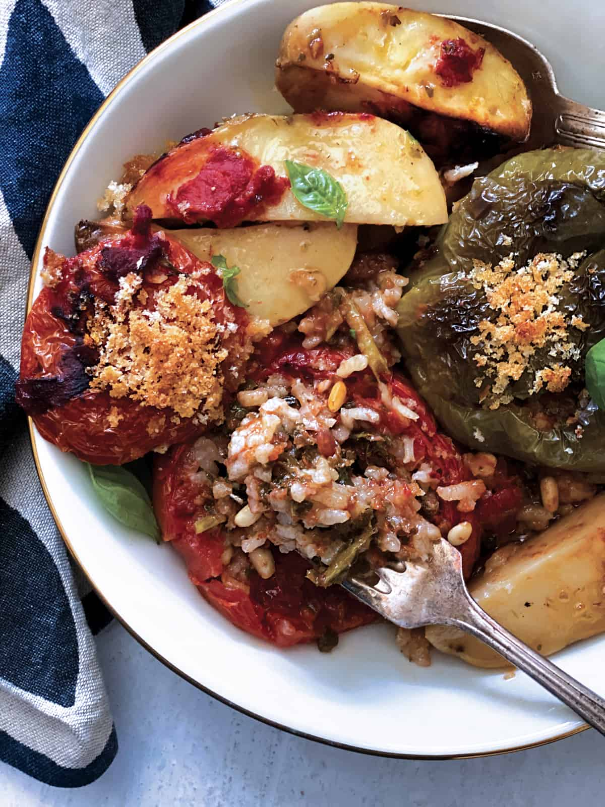 A plate with a stuffed tomato and a green bell pepper, potatoes, fresh herbs and a fork with some rice stuffing.