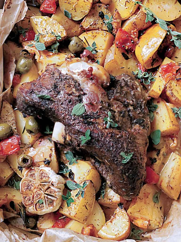 A lamb roast with potatoes, tomato, olives and garlic in parchment paper in a pan.