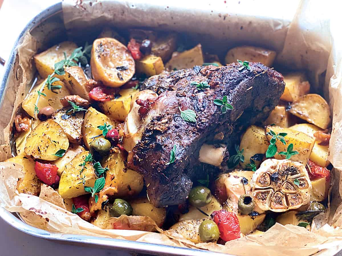 A leg of lamb roast with potatoes, tomato, olives and garlic in parchment paper in a pan.