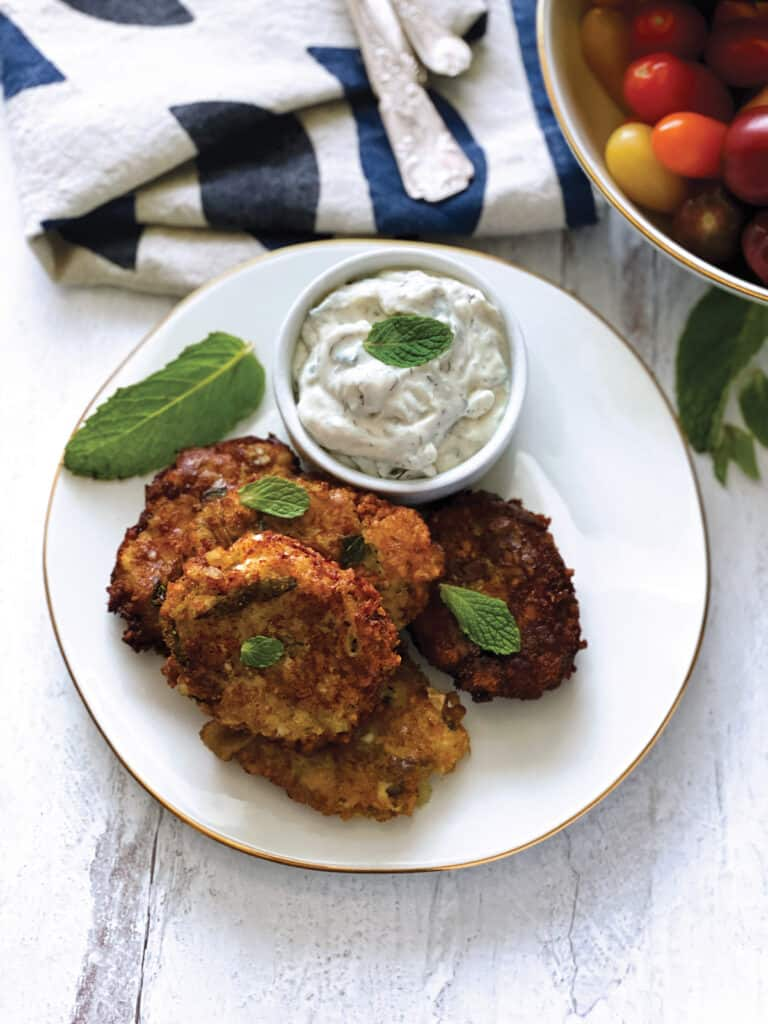 Four eggplant fritters on a plate with a container with yogurt dip, some fresh basil leaves and a cloth napkin at the back.