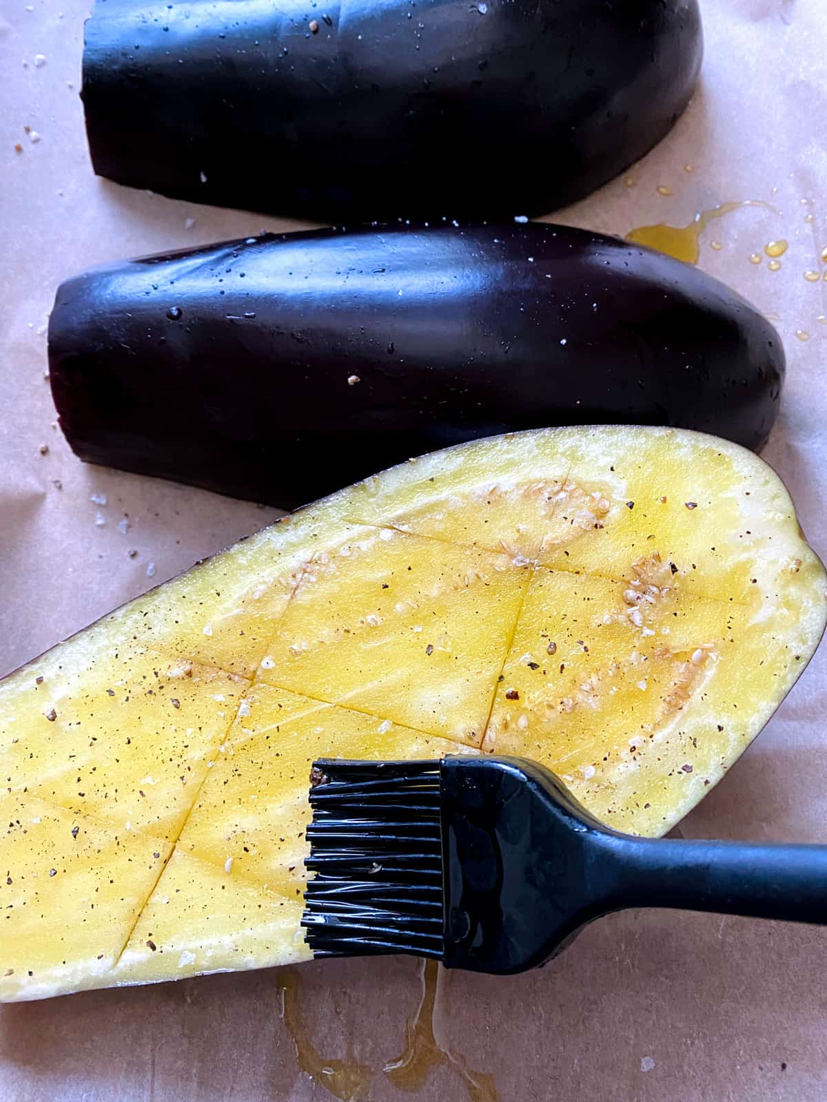 A half of an eggplant, being brushed with olive oil. Two halves at the back, upside down on parchment paper.