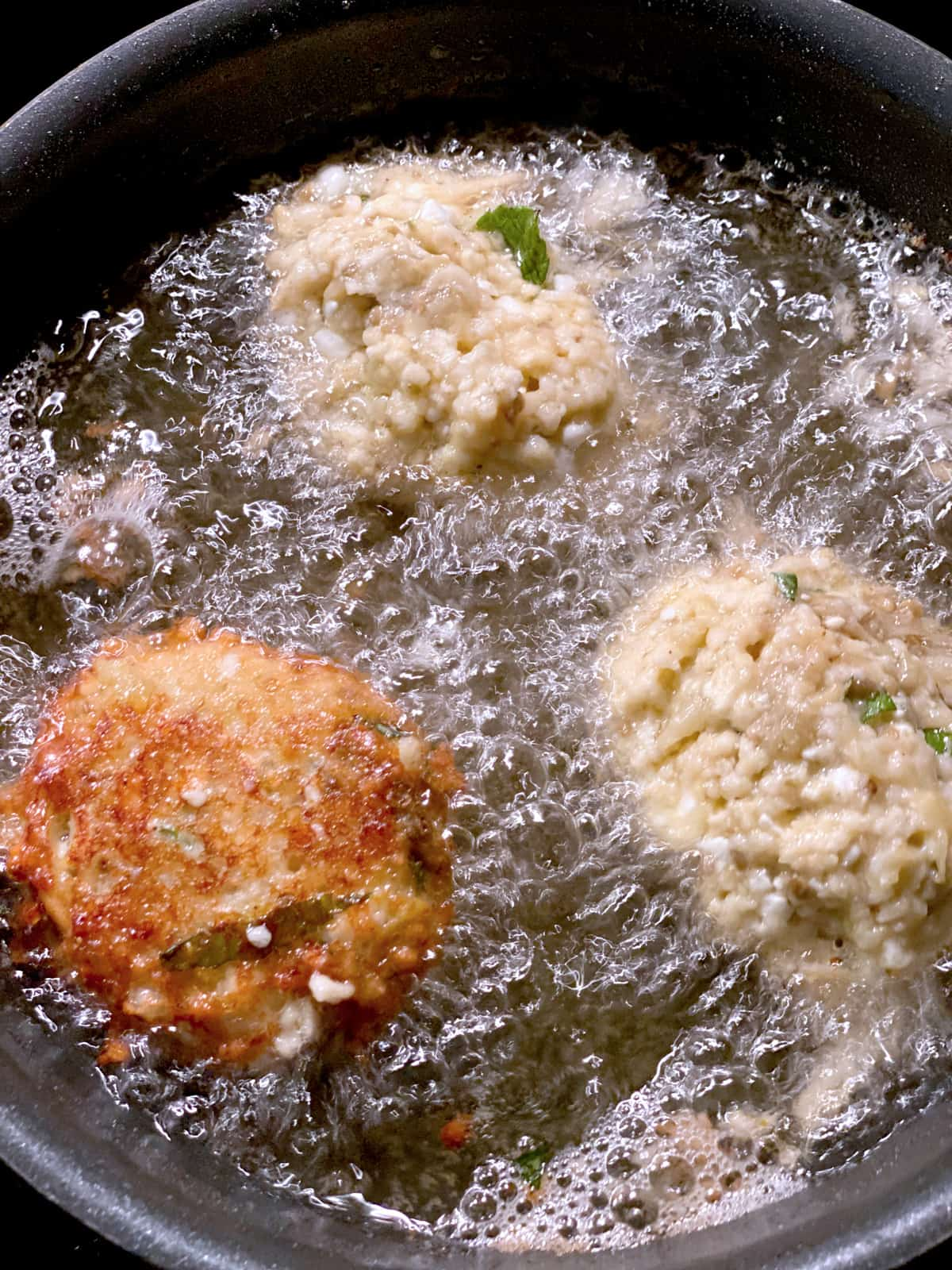 Three eggplant fritters frying in olive oil.