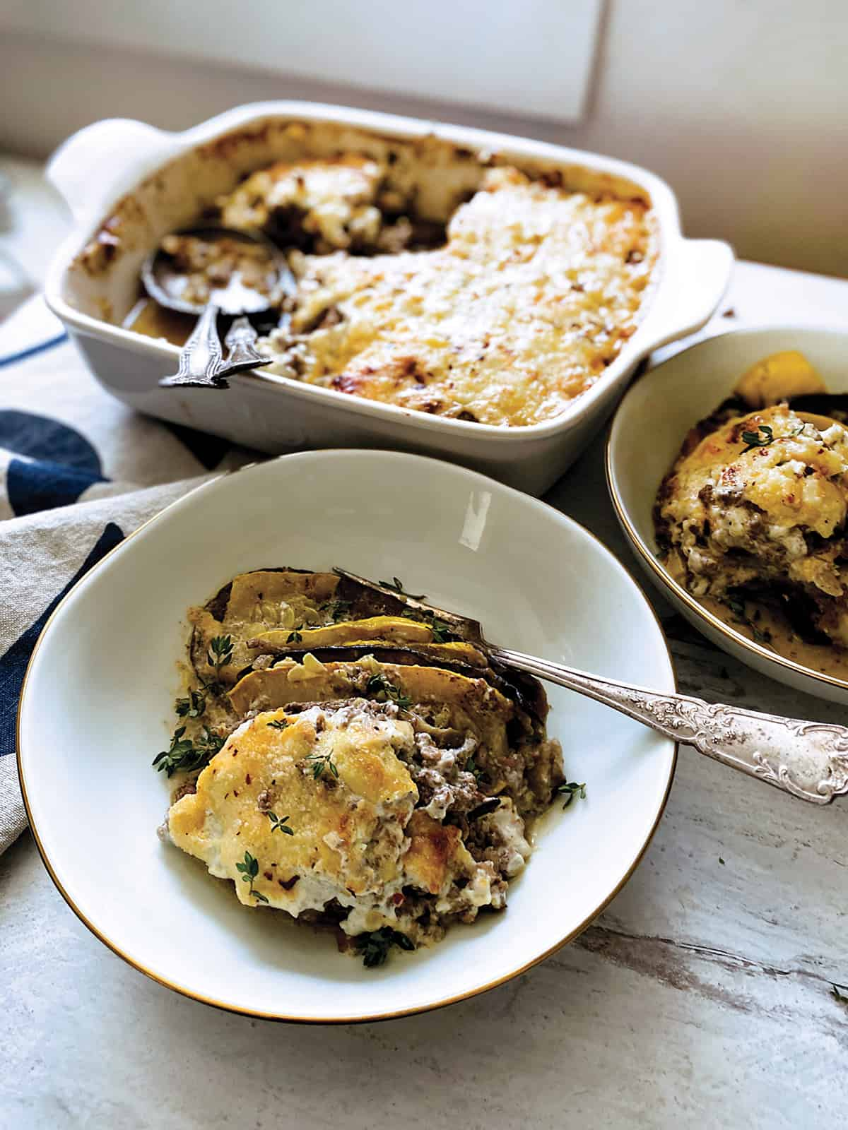 A pan with keto moussaka and two serving utensils, a plate with one piece and a fork and partial view of another plate with moussaka.
