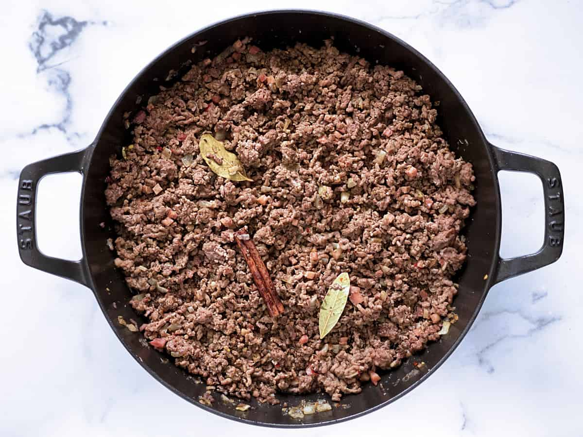 A black skillet with sautéed ground beef,  diced onions, garlic and cubed pancetta. Two bay leaves and a cinnamon stick.