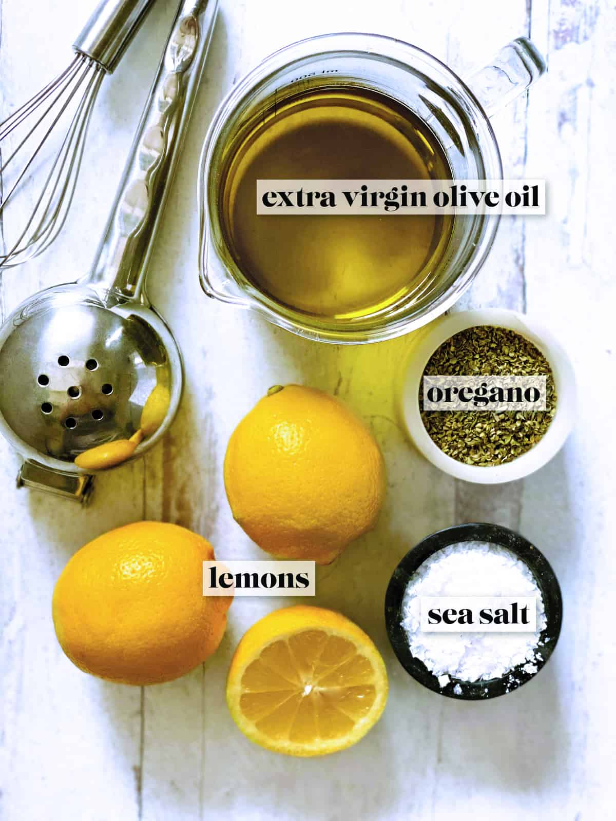 A glass jar with olive oil, a citrus juicer, a small whisk, 2 lemons and one half lemon, a pot with sea salt and another with dry oregano.