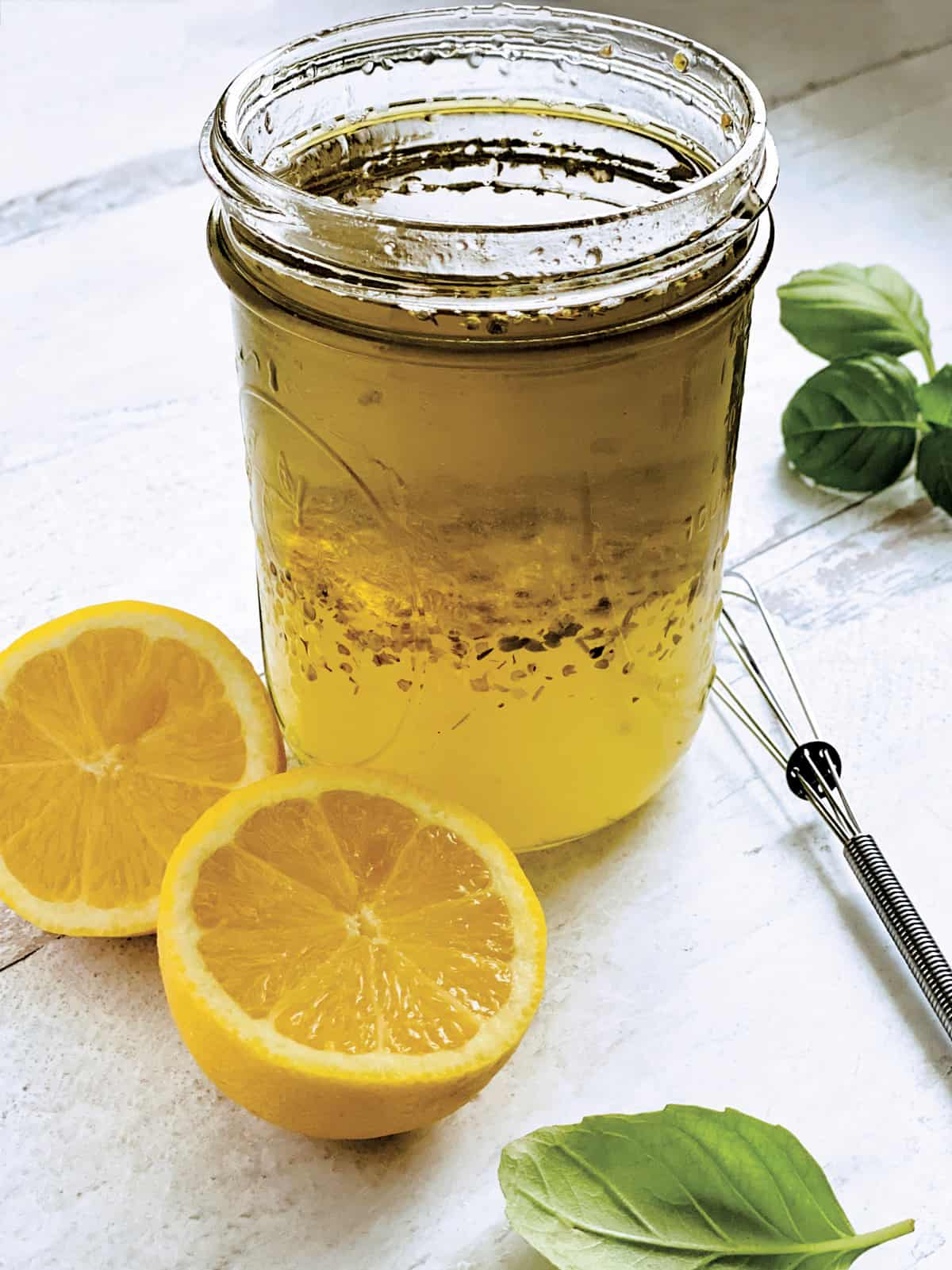A glass jar with lemon and olive oil dressing-ladolemono, two lemon halves, a whisk and some fresh basil.