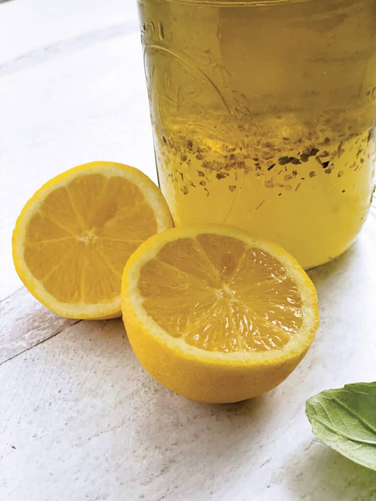 The bottom of a glass jar with lemon and olive oil dressing-ladolemono, two lemon halves, and some fresh basil.
